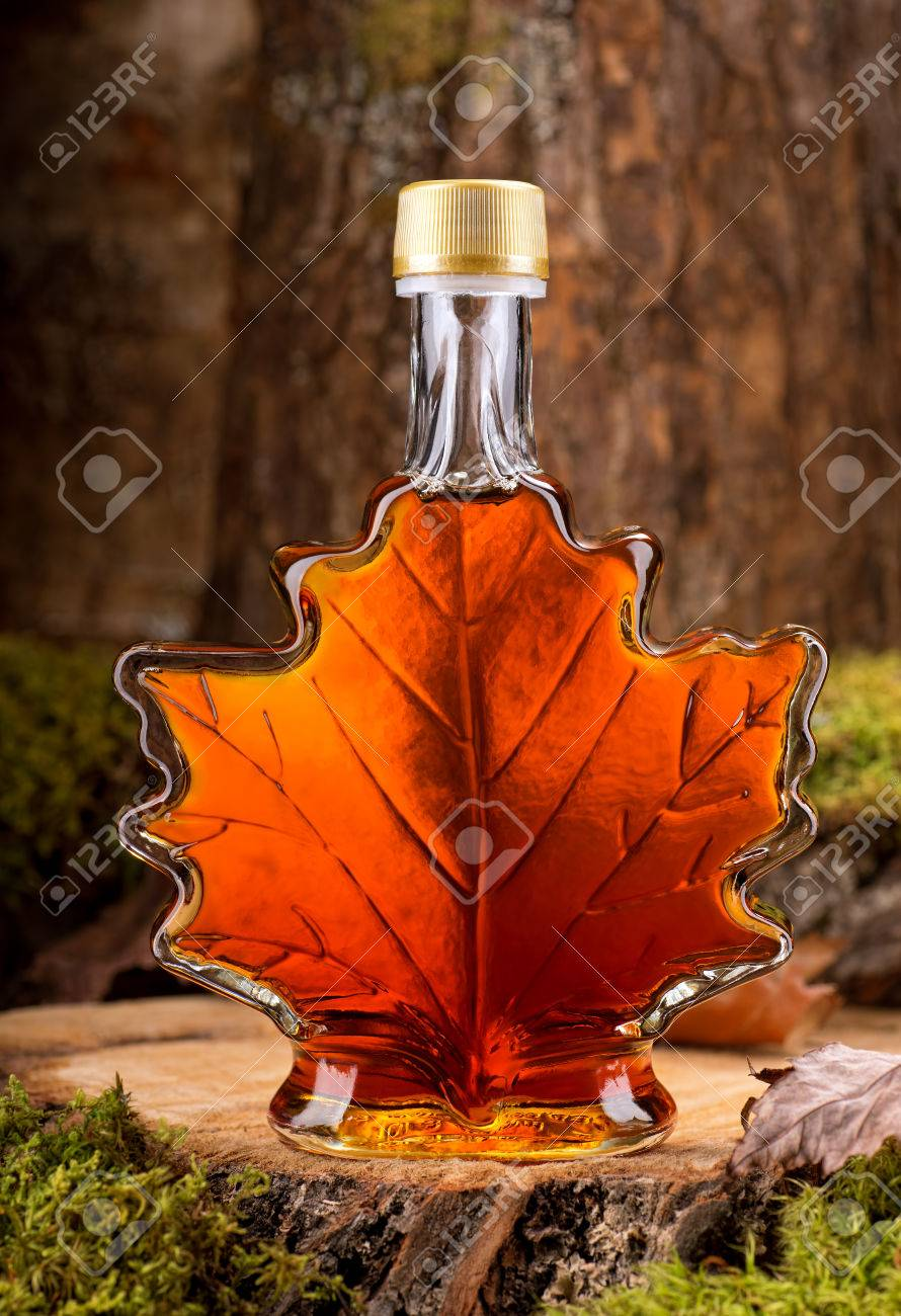 23b5e58a365 A bottle of delicious maple syrup in hardwood forest setting. Stock Photo -  35008235