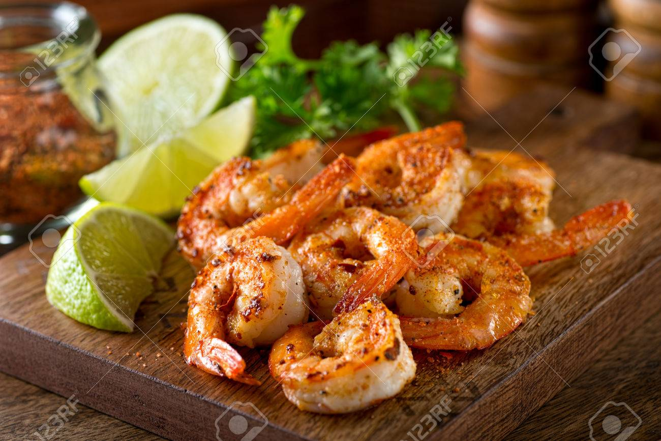 Delicious sauteed shrimp with cajun seasoning and lime on a maple plank. - 63047556