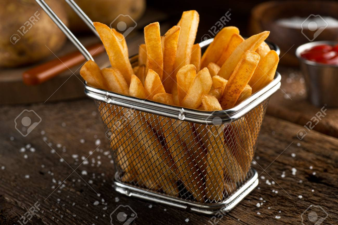 Crispy delicious french fries in a fryer basket. - 86581862