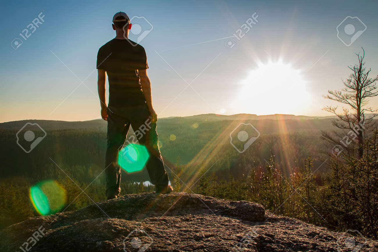 Young man stand on rock with forest and pond, looking to valley - 122350769