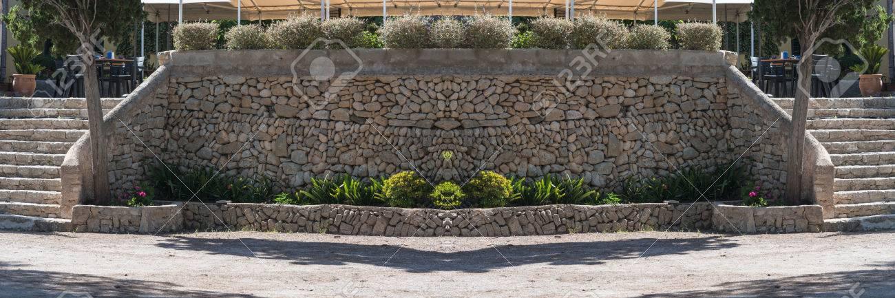 Muro De Contención Mediterráneo De La Piedra Natural Tradicional Para Una Terraza De Un Restaurante