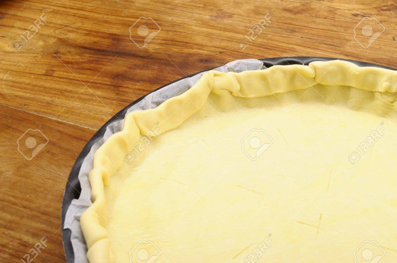Ready-made puff pastry in pie dish on wooden table Stock Photo - 15604680