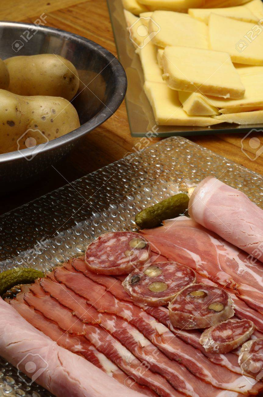 Close Up Of Raclette Cheese With Meats Ham Sausage And Potatoes