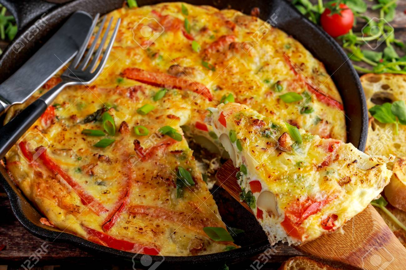 Frittata made of eggs, potato, bacon, paprika, parsley, green peas, onion in iron pan. on wooden table - 66478527