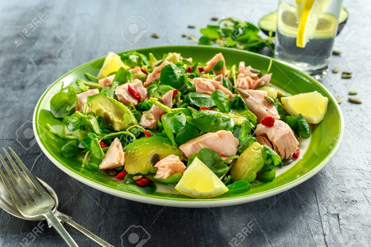 Healthy Salmon, Avocado salad with watercress and goji berries, pumpkin seed mix on green plate - 73562313