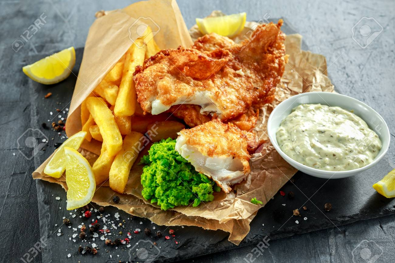 76106582-british-traditional-fish-and-chips-with-mashed-peas-tartar-sauce-on-crumpled-paper-.jpg