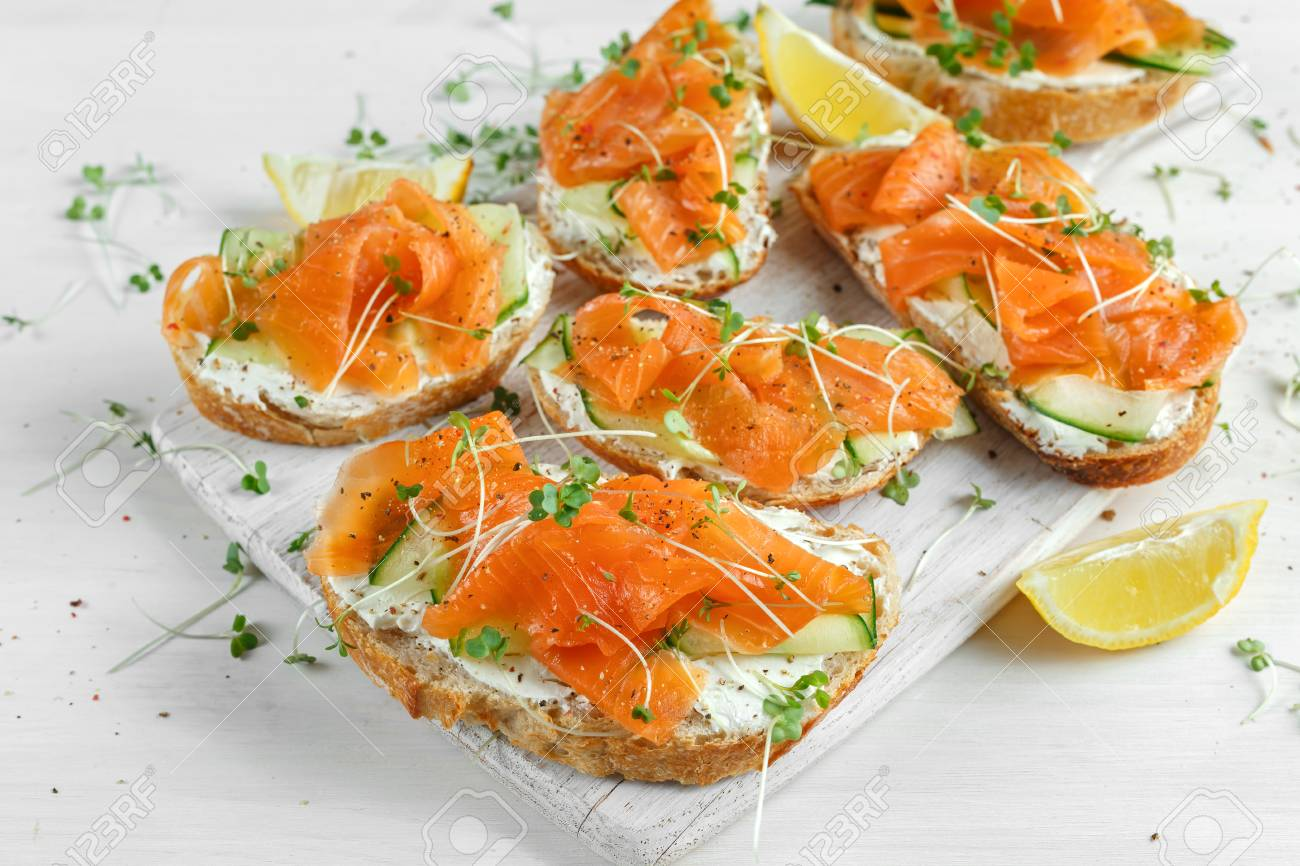 Smoked salmon bruschettas with soft cheese and cucumber shavings on white board. - 77624351