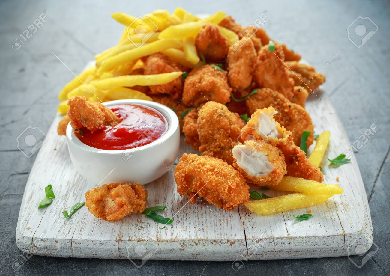 Fried crispy chicken nuggets with french fries and ketchup on white board - 80026048