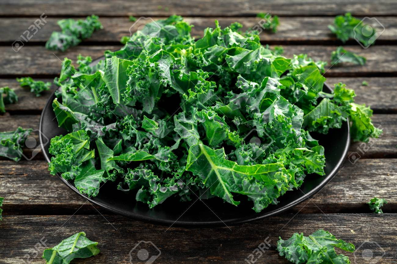 Fresh green healthy superfood vegetable kale leaves in a black plate on wooden rustic table - 80551946