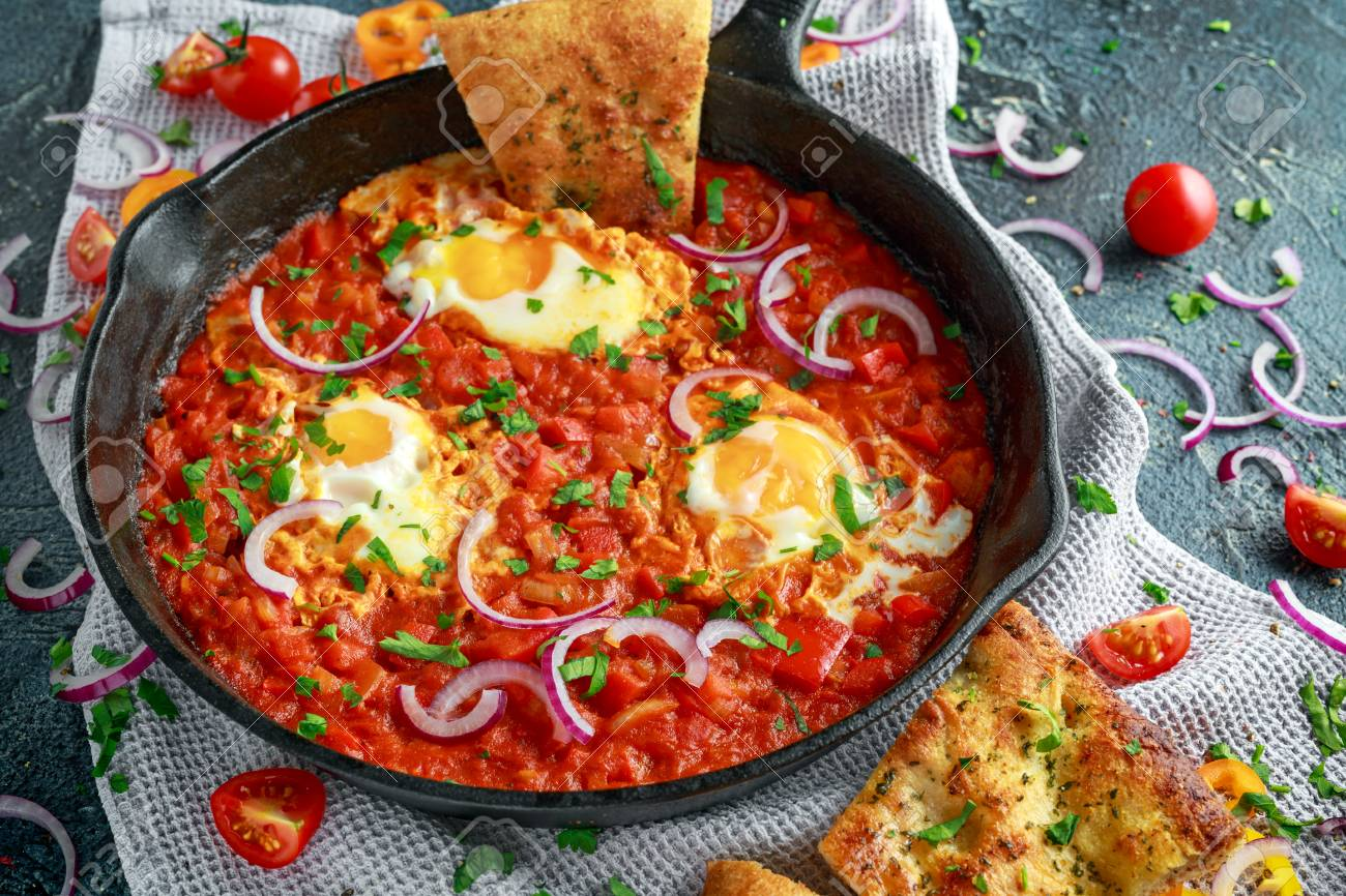 Tasty Breakfast Shakshuka in a Iron Pan. Fried eggs with tomatoes, red, yellow peppers, onion, parsley, Pita bread and herbs. Healthy Food - 85765565
