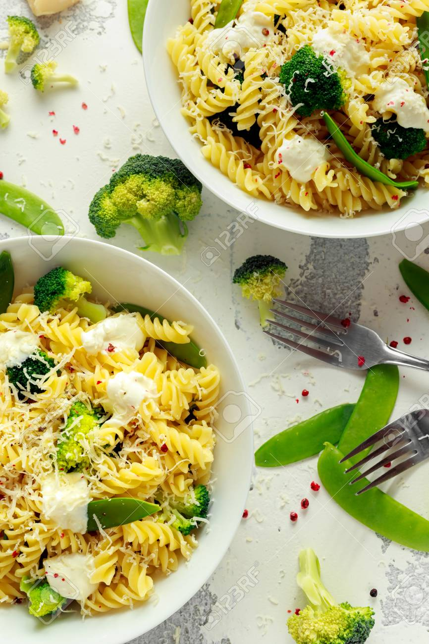 Pasta with green vegetables broccoli, Mange tout and creamy sauce in white plate - 91656184