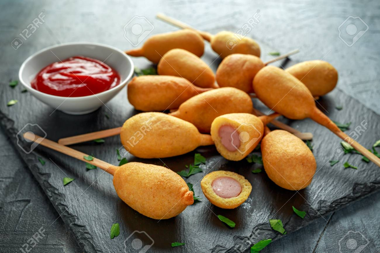 Corn Dogs on stone platter with ketchup - 94825428