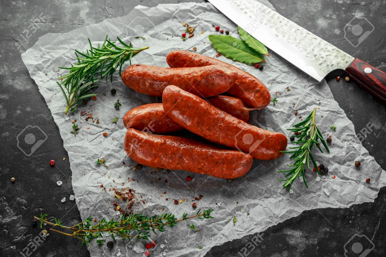 Freshly made raw breed butchers sausages in skins with herbs on crumpled paper. - 97489238