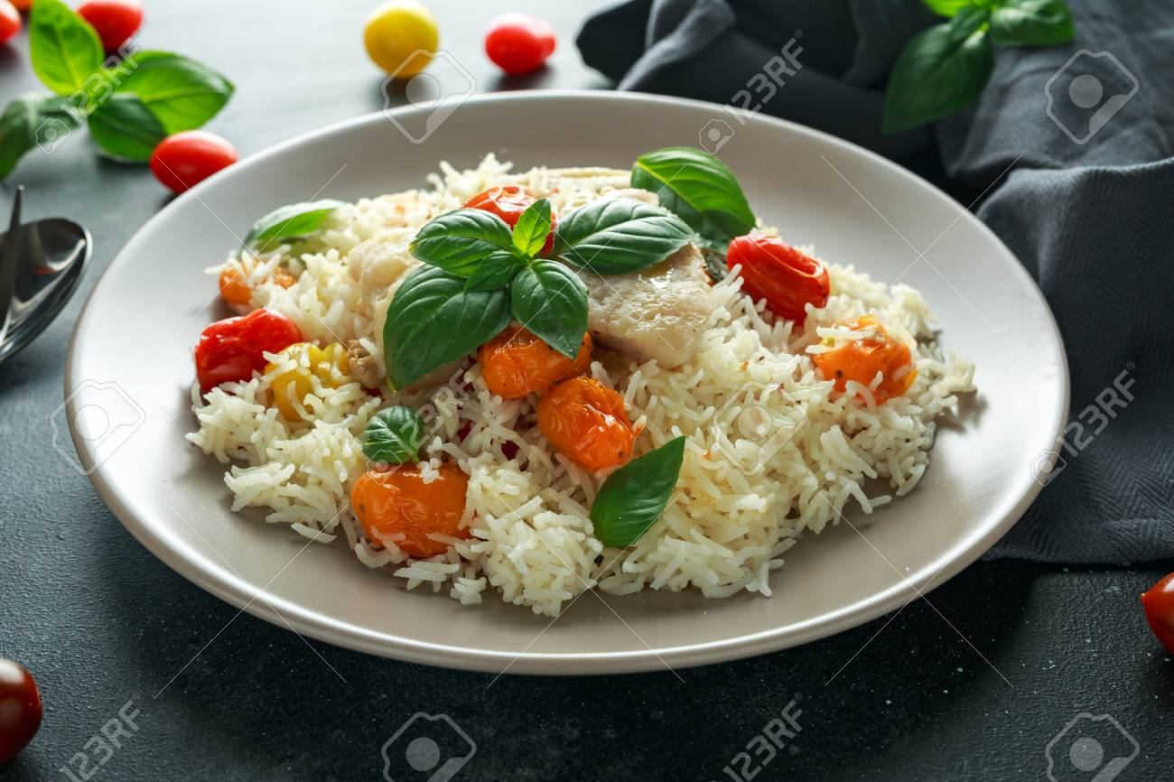 Steamed cod fish with rice and cherry mix tomatoes and basil herbs in a plate - 103953232