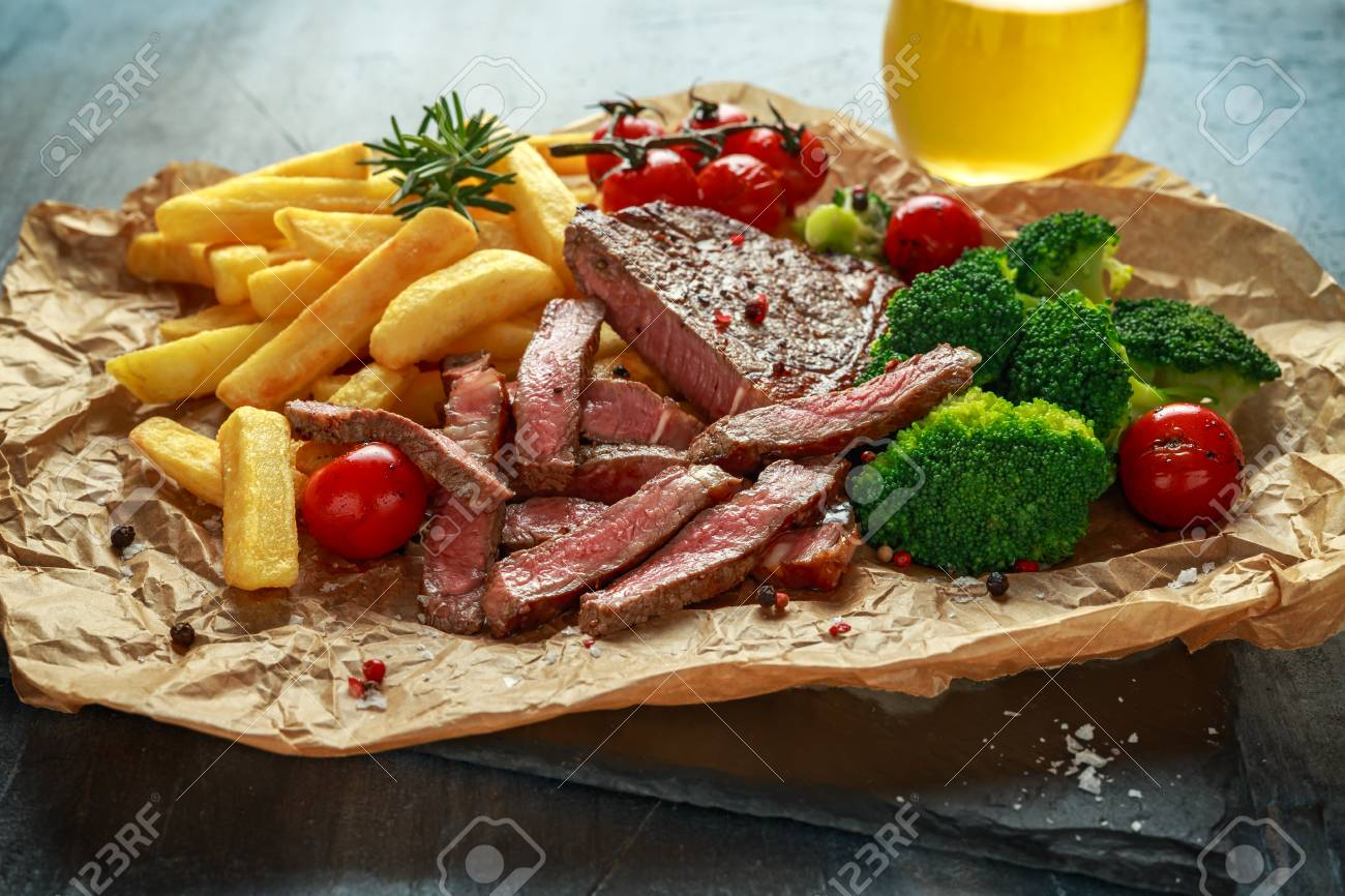 Grilled sirloin steak with potato fries, broccoli, beer and cherry tomatoes on crumpled paper - 108608821