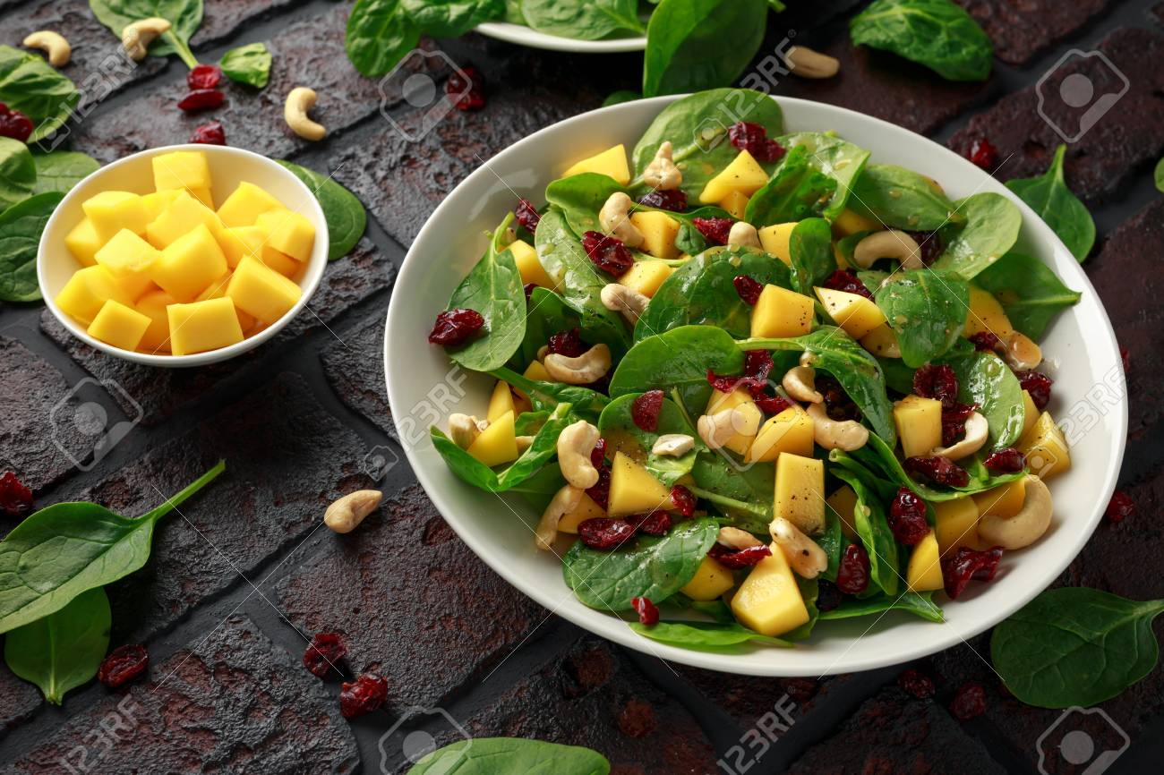 Mango Spinach salad with dried cranberries and nuts. healthy food. - 117671120