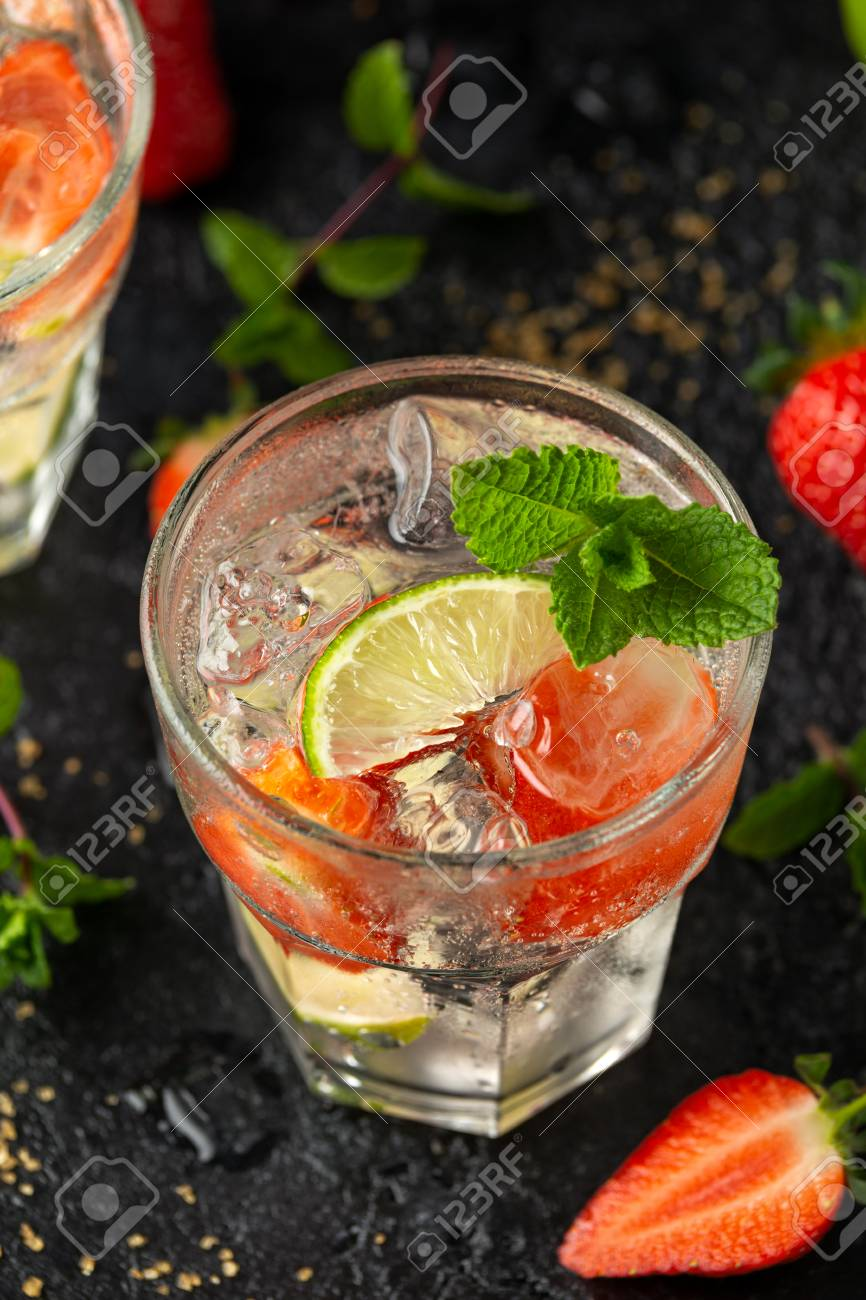 Strawberry Mojito cocktail with Rum, lime and mint in glass. Summer cold drink with ice. - 122798369