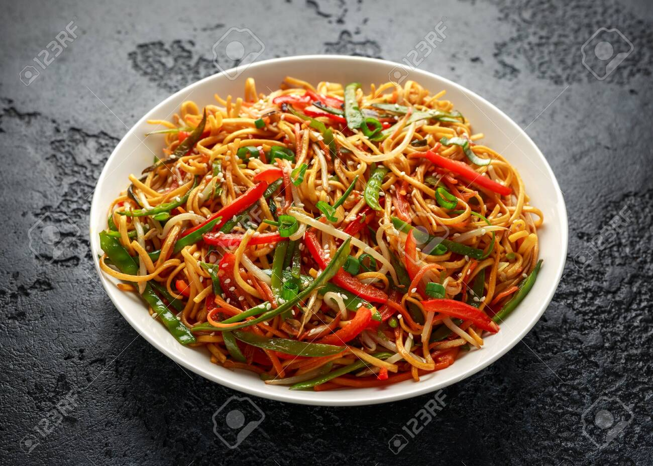 Chow mein, noodles and vegetables dish with wooden chopsticks - 123674904