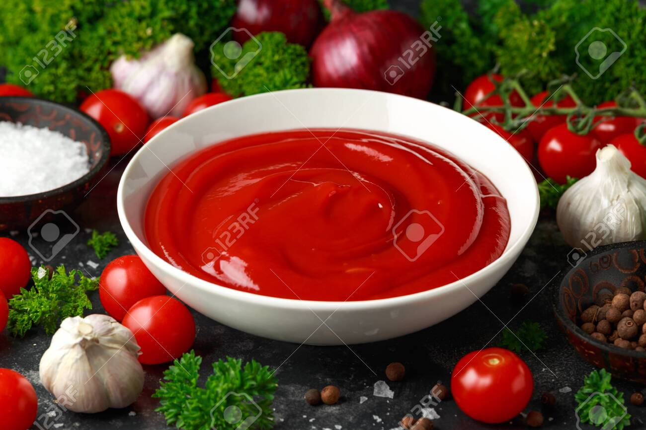 Homemade ketchup sauce in white bowl with vegetables and herbs - 124336062