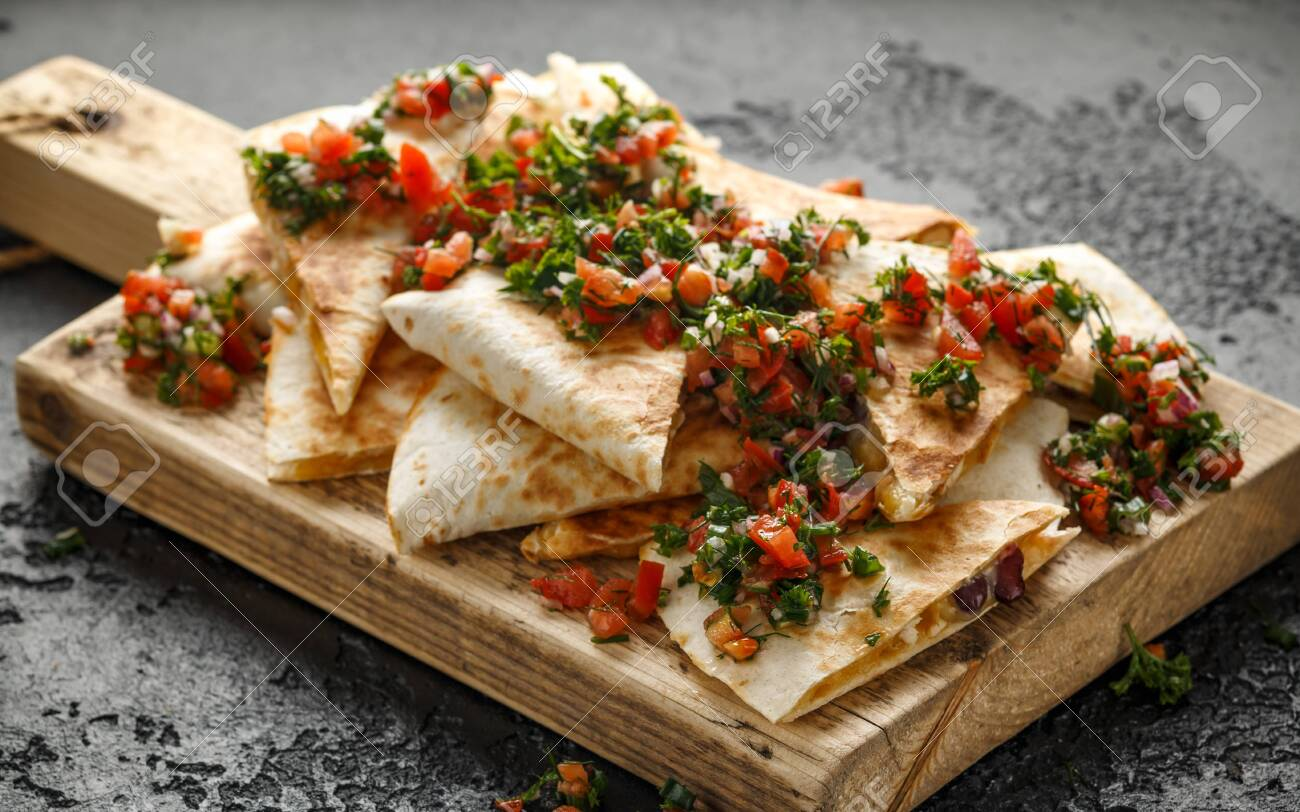 Mexican food quesadillas with chicken and cheese served on rustic wooden chopping board with homemade fresh salsa topping - 128852745