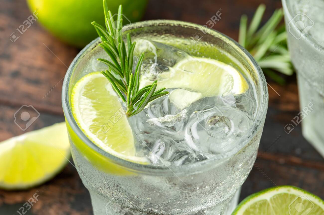 Gin and Tonic Alcohol drink with Lime, Rosemary and ice on wooden table. - 129859271