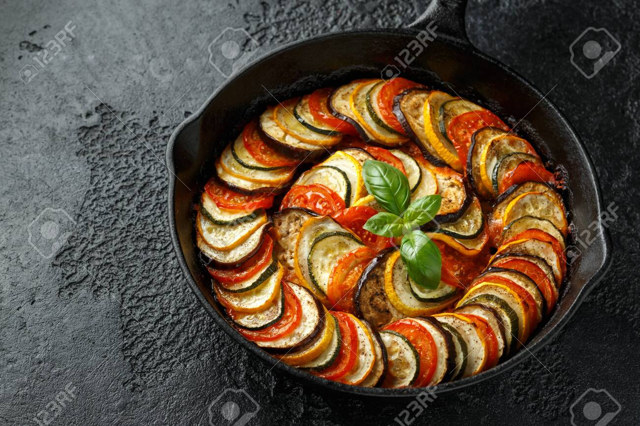 Ratatouille Vegetable Stew with zucchini, eggplants, tomatoes, garlic, onion and basil. on cast iron pan. Traditional French food - 129859280