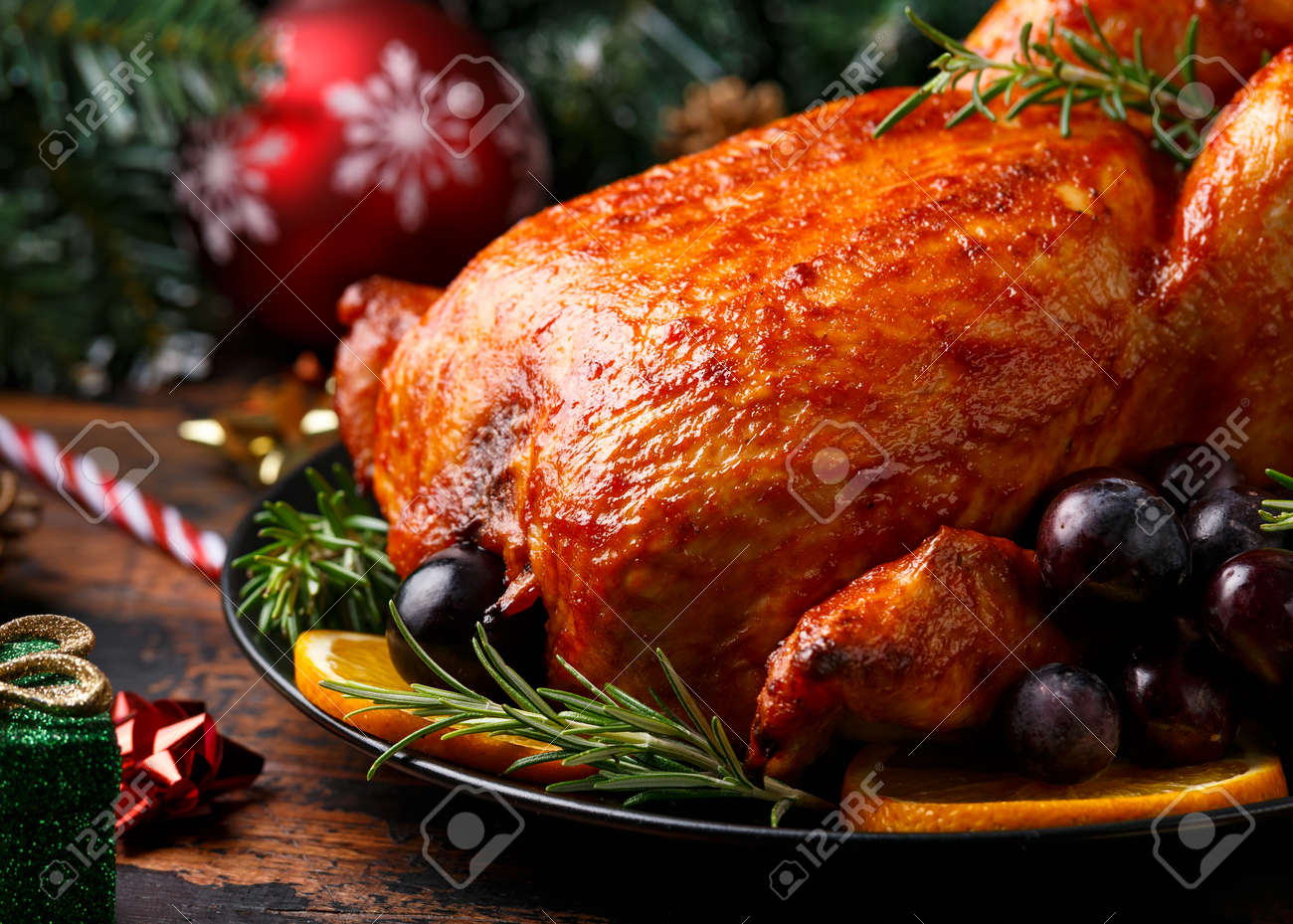 Christmas Chicken, roast in oven with decoration, gifts, green tree branch on wooden rustic table - 158220625