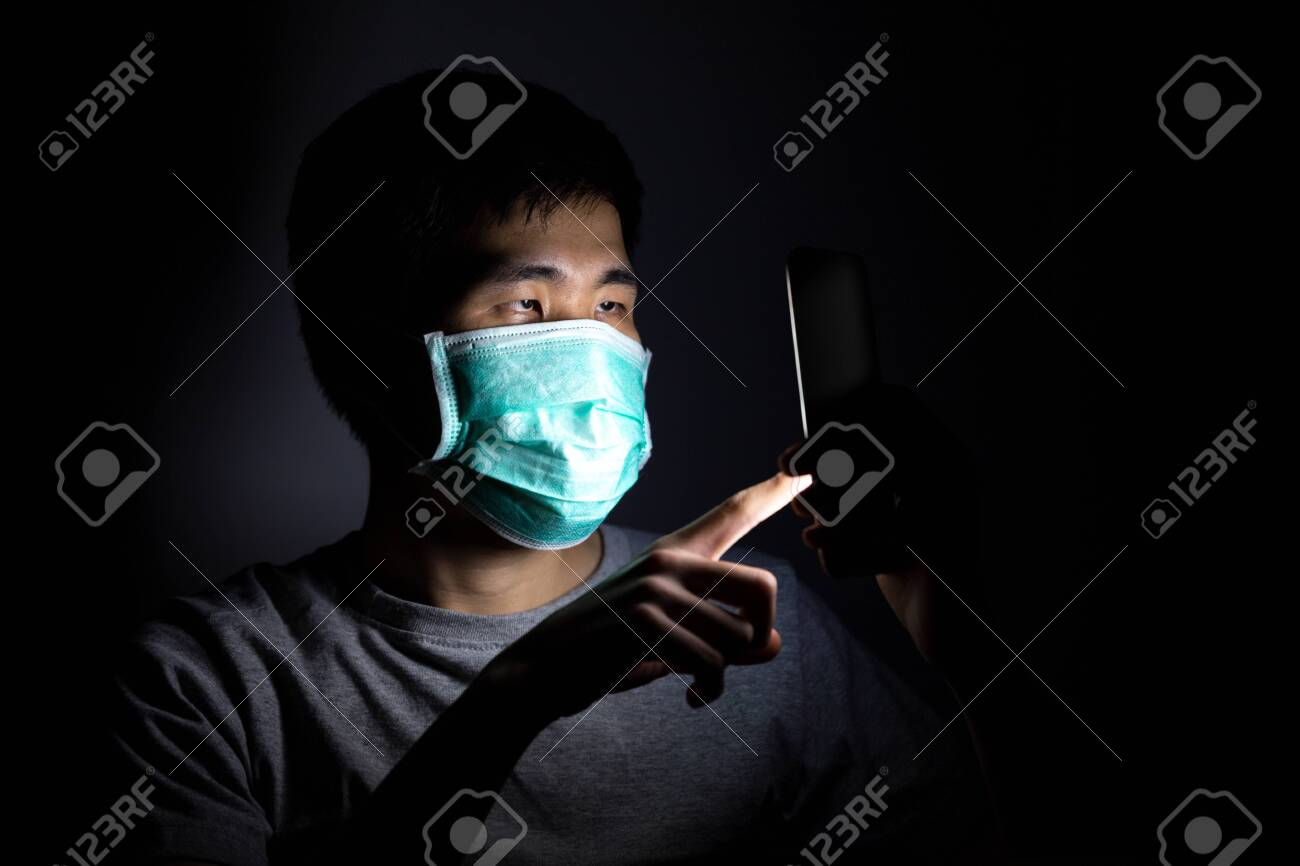 Asian man using smart phone work from home and wear a protective medical mask to prevent Coronavirus (CoVID-19) outbreak. - 148925437