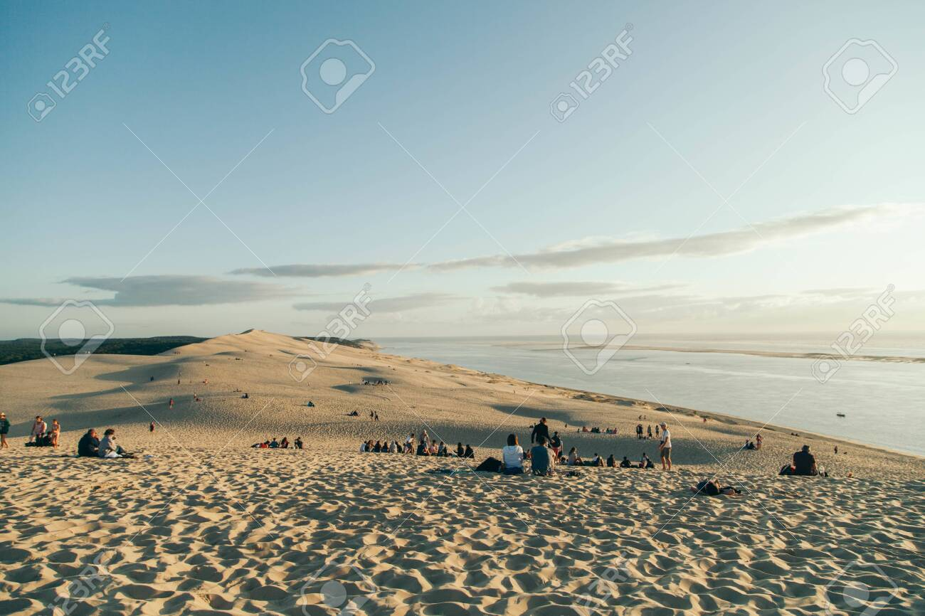 Panorama of the crowded Dune du Pilat at sunset - 134134423