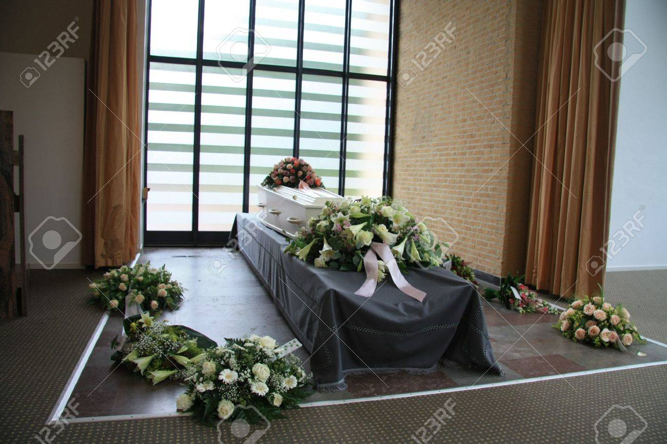 White casket covered with floral arrangements at a funeral service stock photo white casket covered with floral arrangements at a funeral service izmirmasajfo