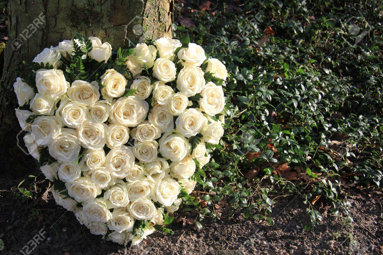 Heart shaped sympathy flower arrangement with white roses near a tree - 12072870