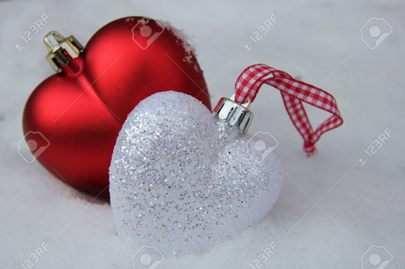 white and red heart shaped ornaments in fresh fallen snow stock