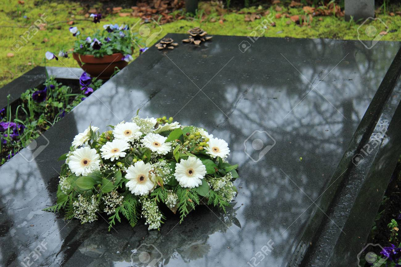 White funeral flowers on a grey marble tomb stock photo picture and stock photo white funeral flowers on a grey marble tomb izmirmasajfo Image collections