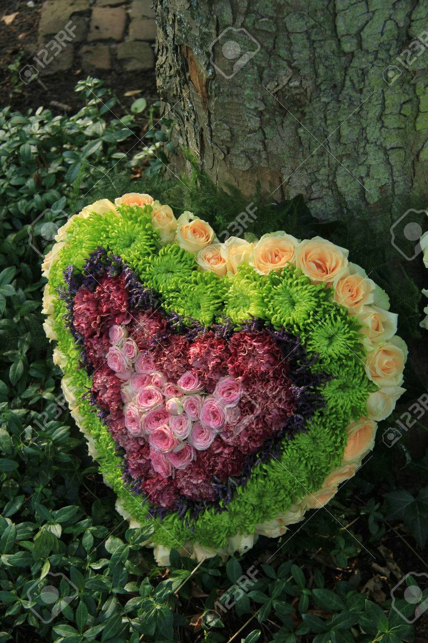 Heart Shaped Sympathy Flower Arrangement In Green Pink And Yellow