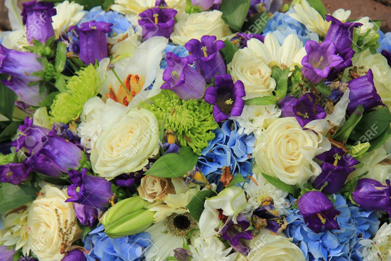 White Roses And Blue Purple Flowers In A Wedding Flower Arrangement