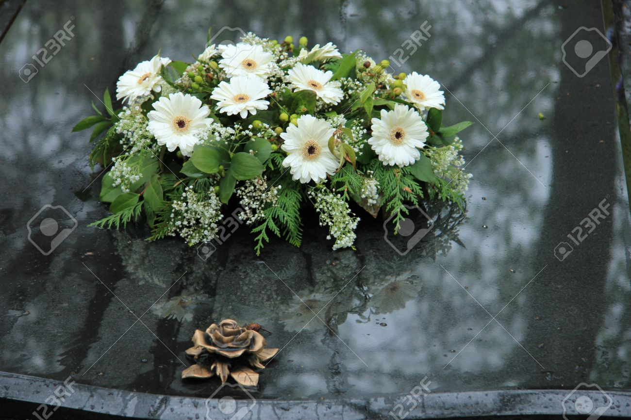White funeral flowers on a grey marble tomb stock photo picture and stock photo white funeral flowers on a grey marble tomb izmirmasajfo Images