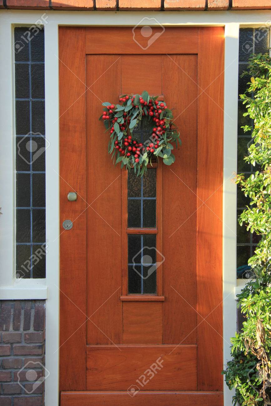 Berry christmas wreath with decorations on a door - 38610073