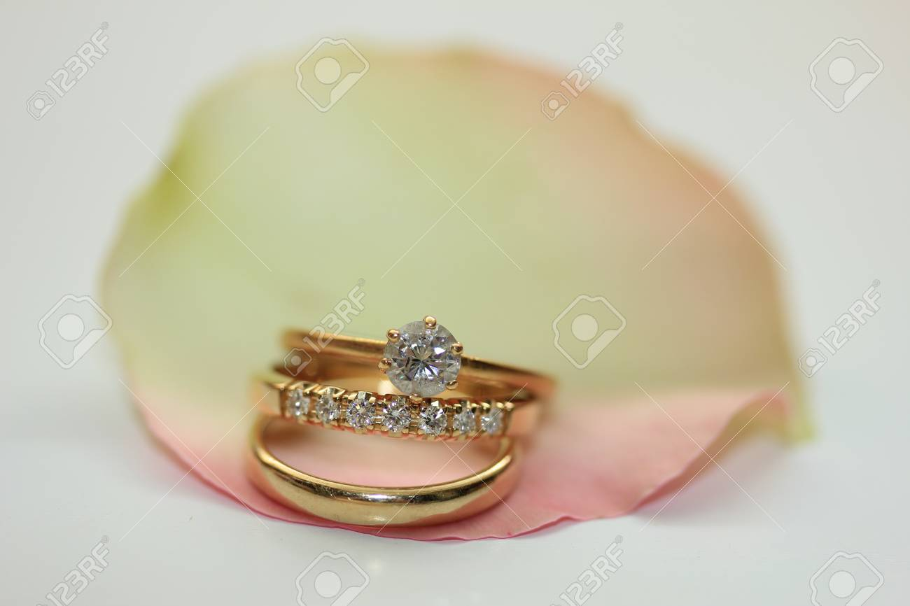 Three Wedding Rings On A Rose Petal Stock Photo Picture And
