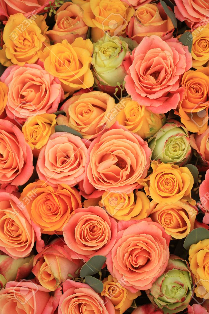 Yellow Orange And Pink Roses In A Floral Arrangement At A Wedding