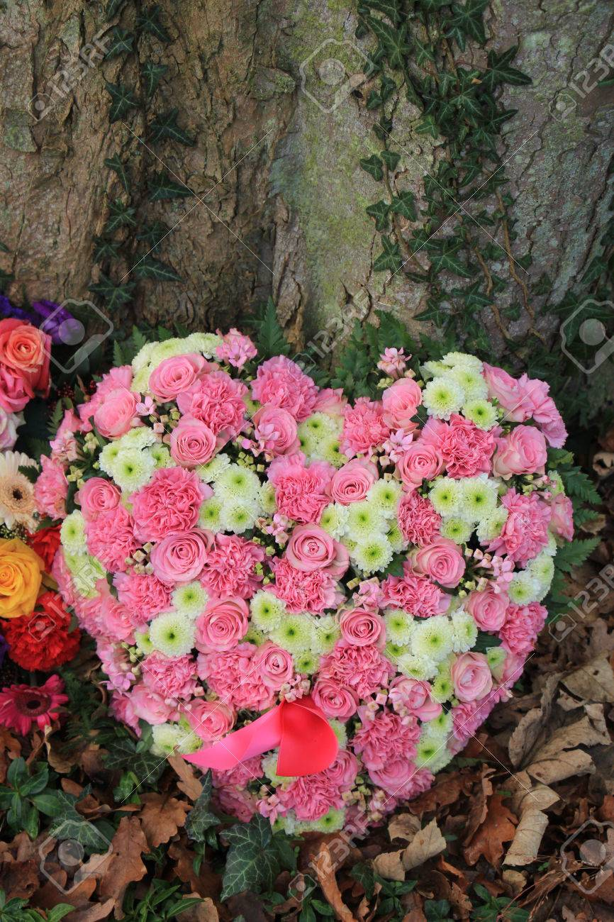 Heart Shaped Sympathy Or Funeral Flowers Near A Tree Stock Photo