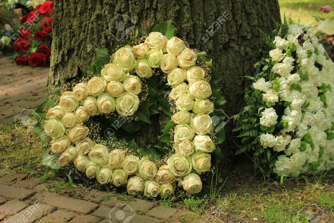 Heart shaped sympathy flowers or funeral flowers near a tree heart shaped sympathy flowers or funeral flowers near a tree white roses stock photo izmirmasajfo