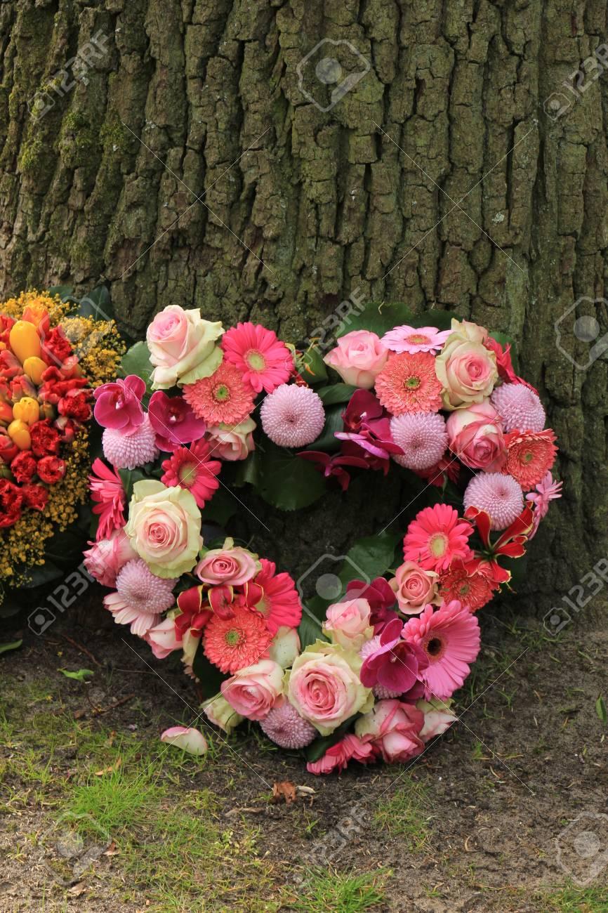 Heartshaped sympathy flowers or funeral flowers near a tree stock heartshaped sympathy flowers or funeral flowers near a tree stock photo 80433209 izmirmasajfo Gallery