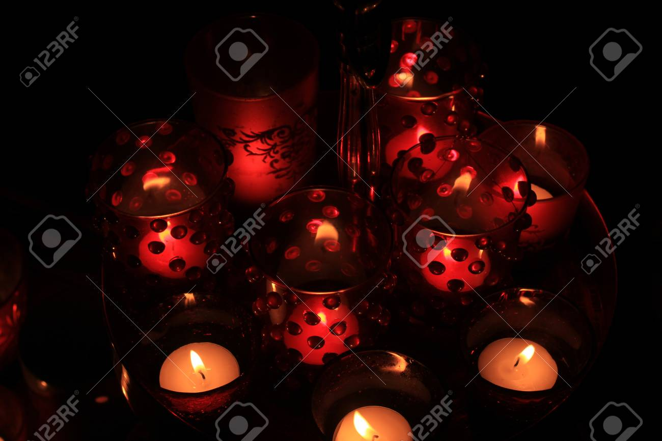 A Christmas Arrangement.Red Candles And Votive Lights Burning In A Christmas Arrangement