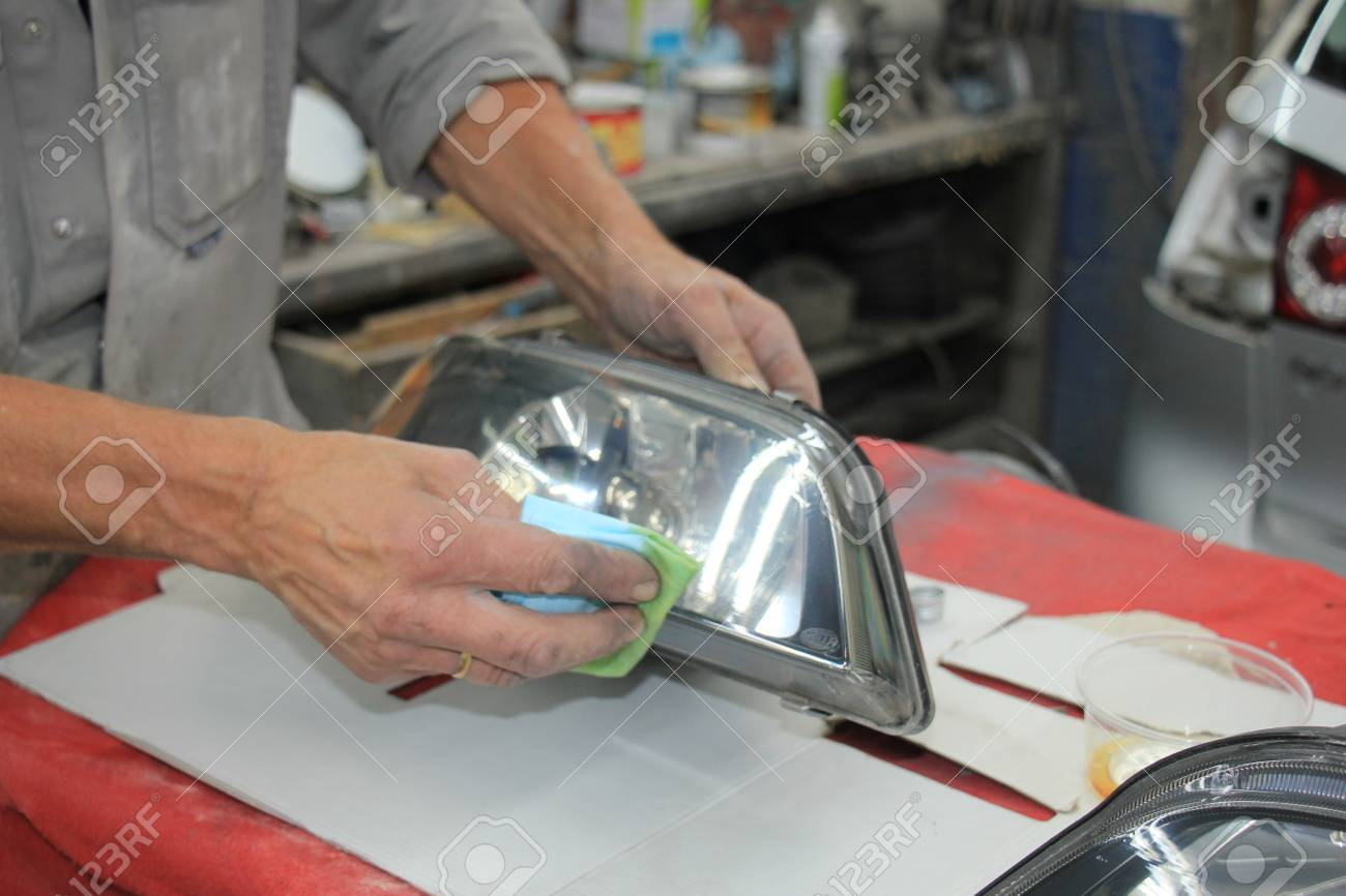Man Refurbishing A Car Headlight With Clear Coating Stock Photo
