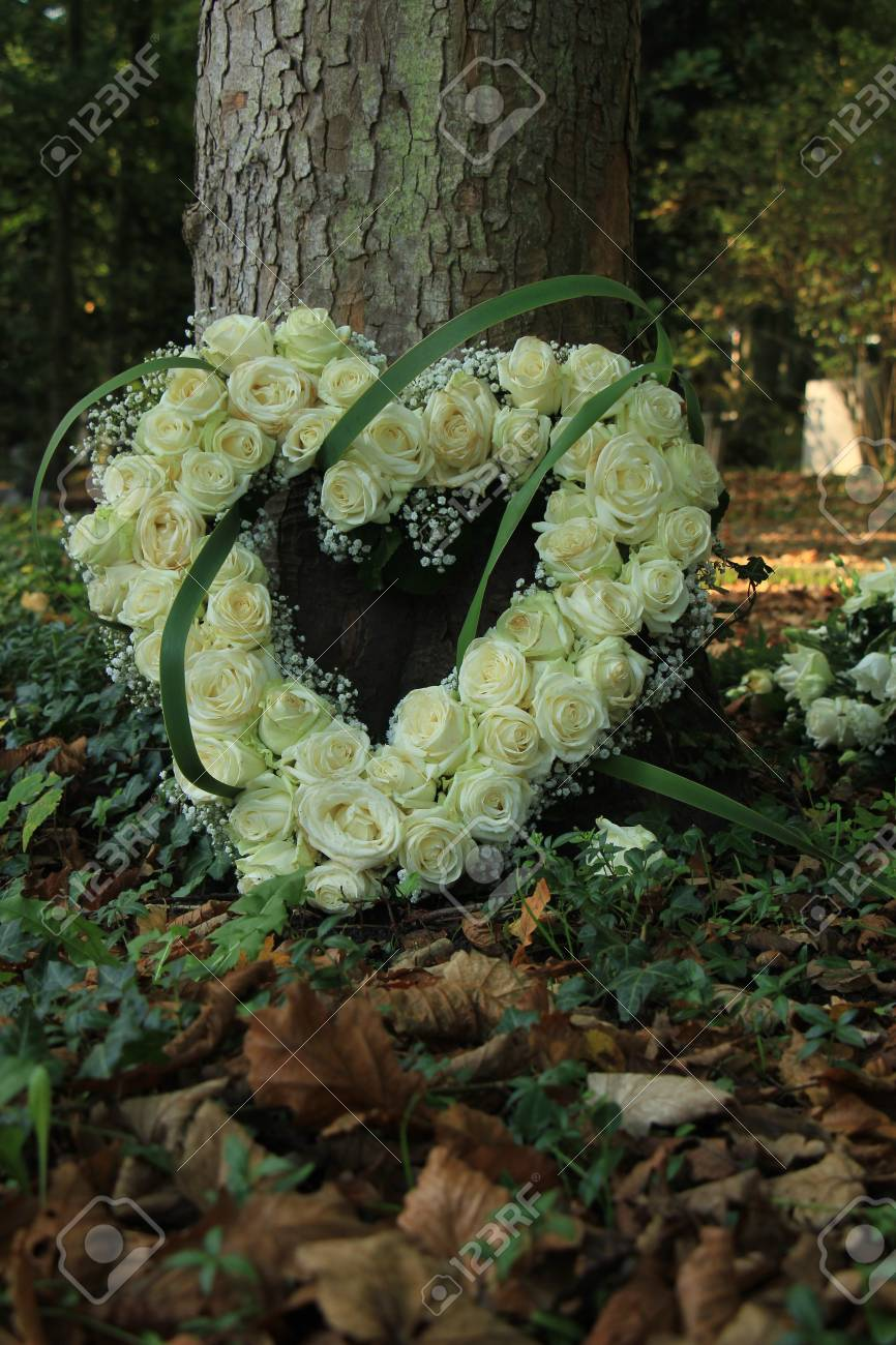 Heart Shaped Sympathy Flowers Made From White Roses Near A Tree