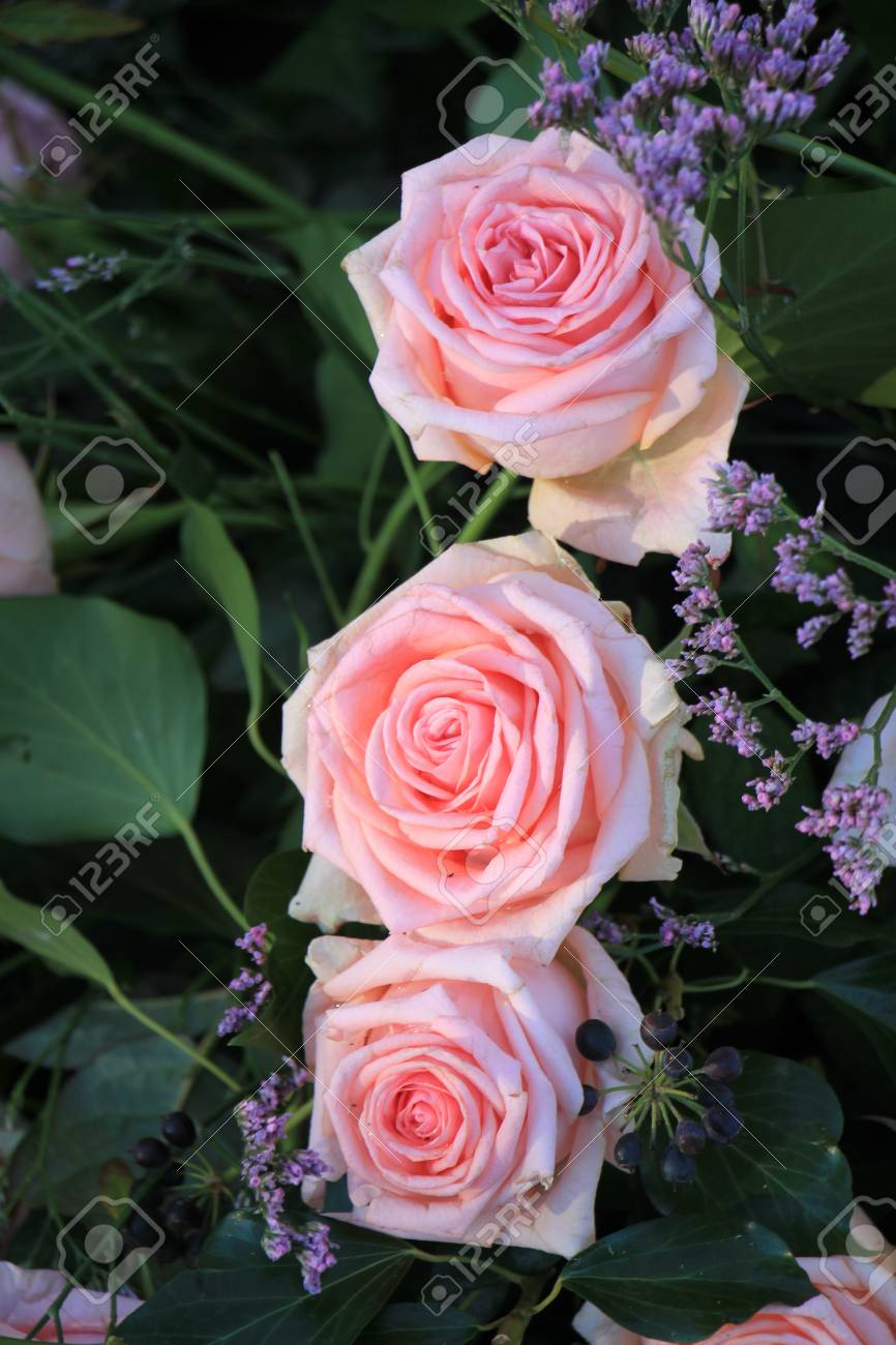 Bridal Flower Arrangement With Pink Roses And Small Purple Flowers