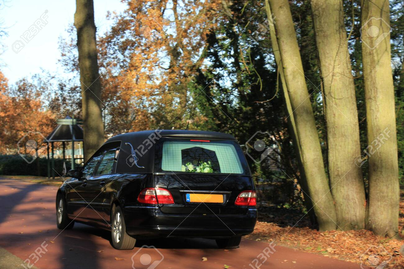 A black hearse on a cemetery in the autumn - 133137521