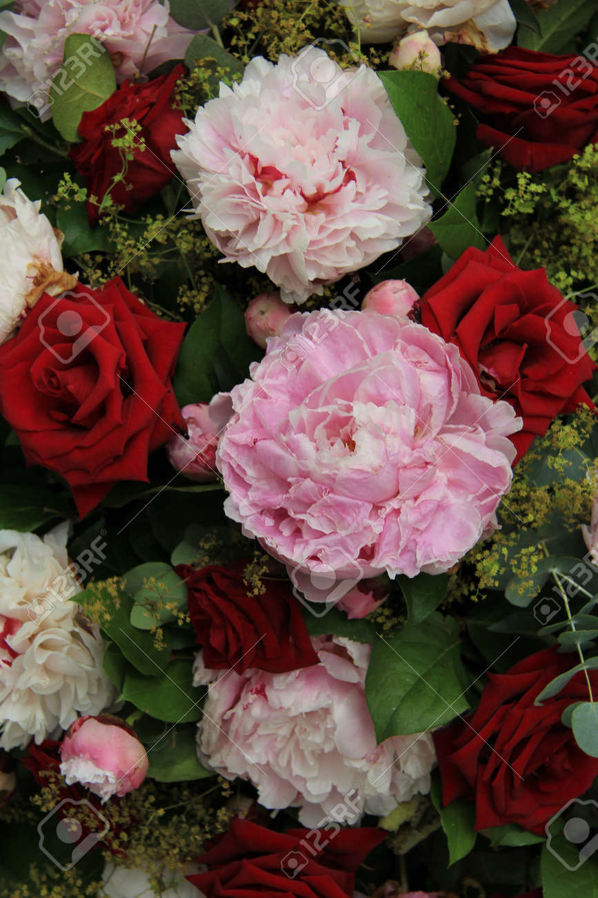 Red roses and pink peonies in a wedding arrangement - 167685137