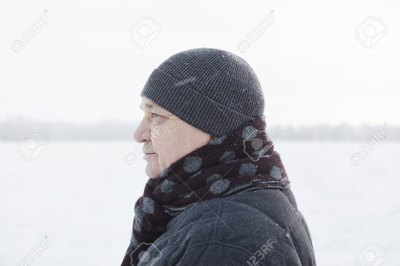 f71f9673500645 Profile portrait of senior man wearing knit cap, scarf and jacket standing  in winter field