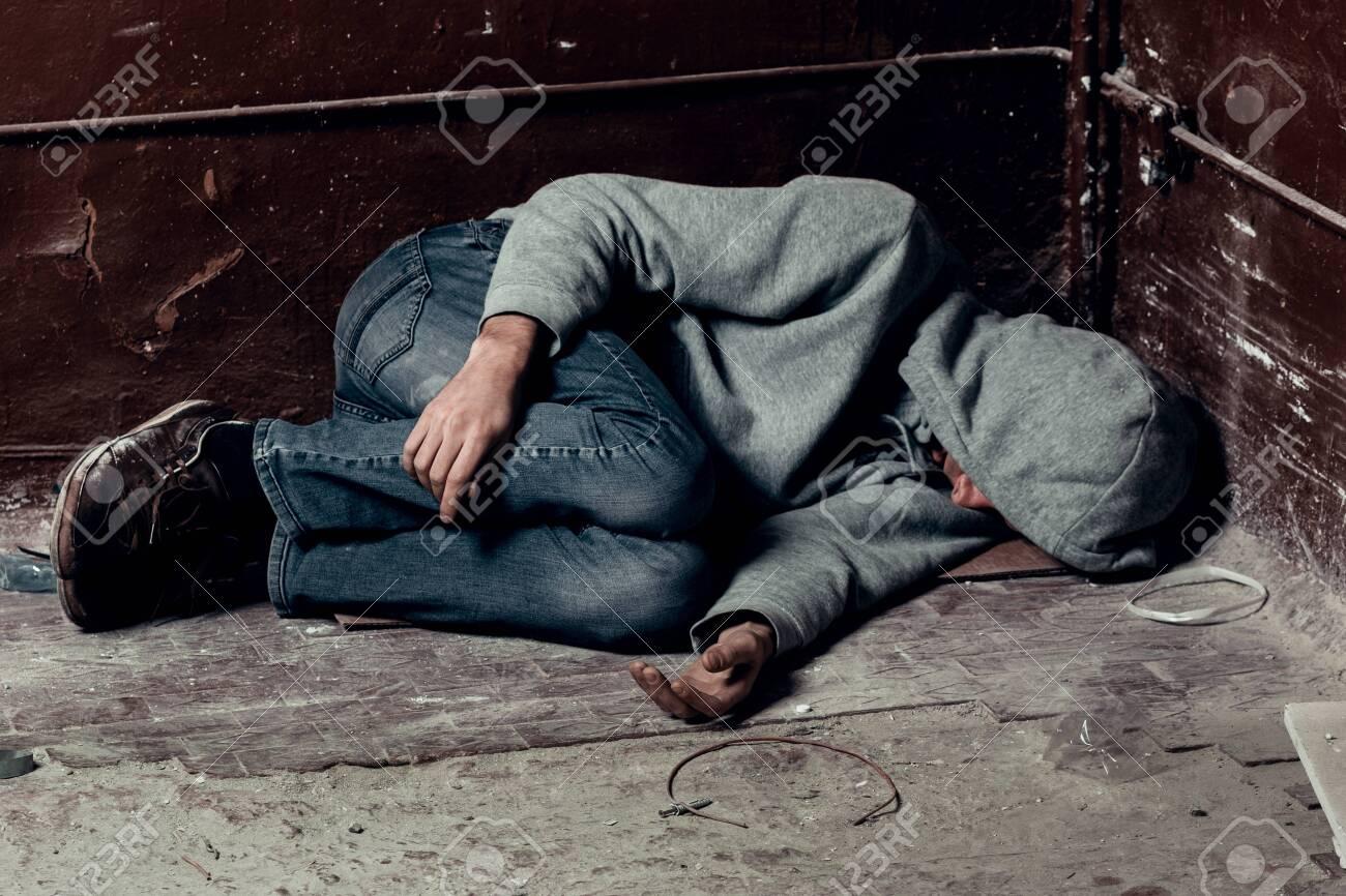 homeless guy sleeps on the floor in the slums. - 126139408